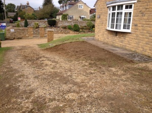 Front bed de-turfed, turf has been stacked by garage upside down to make nutrient rich soil for raised beds later on