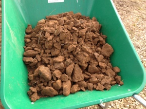 A wheelbarrow full of rocks, two barrow loads per strip  are coming out